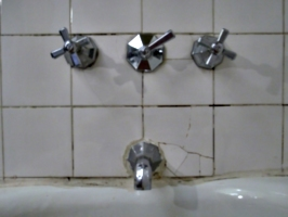 [picture: Faucets and cracked tiles]
