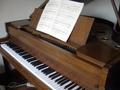 [Picture: Baby grand piano]