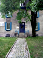 [picture: Cobbled path through grass past tree to blue door in grey stone building.]