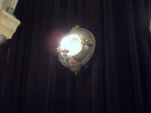 [Picture: porthole mirror lamp with candle, lit up]