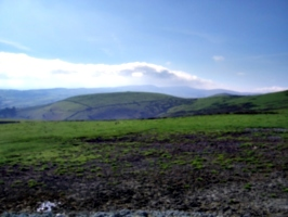 [picture: Muddy field and green hill]