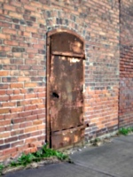 [picture: Rusty metal door in a brick wall]