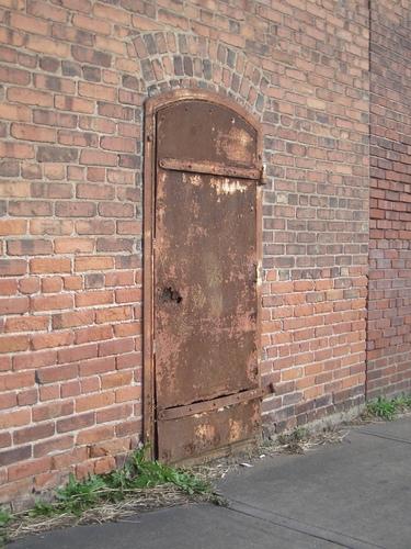 [Picture: Rusty metal door in a brick wall]