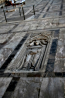 [picture: bas-relief gravestone in the floor]