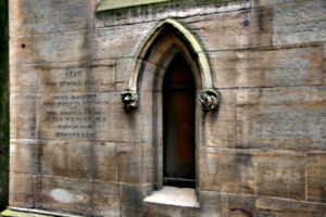 [picture: Arched stone window with carvings and inscription]