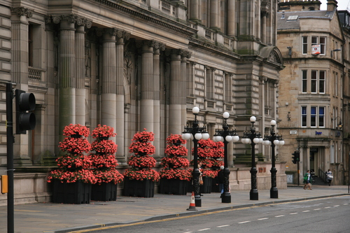 [Picture: Neoclassical entrance with carefully manicured flowers]