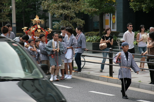[Picture: Child with staff leading the mikoshi]